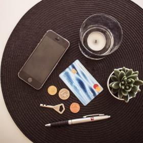 En mobiltelefon, nyckel, mynt, banktkort, blomma och ljus på ett bord.