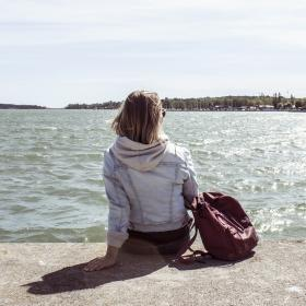En tjej som sitter på en brygga och tittar ut över vattnet en solig dag.