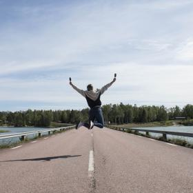 En flicka som hoppar på en väg.