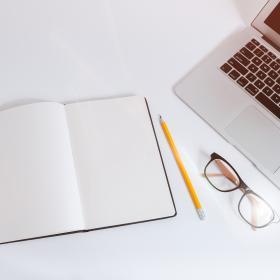 Ett bord med en telefon, ett anteckningsblock och penna, ett par glasögon och en dator.