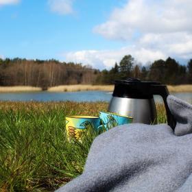 Två kaffekoppar och en termos på en filt i gräset.