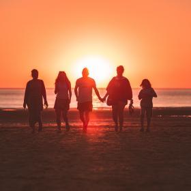 Fem personer går på en strand i solnedgången.