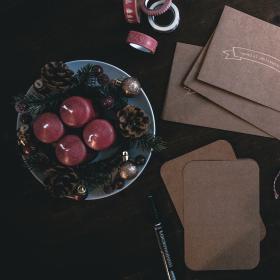 Ett bord med röda ljus, kuvert och kort, en penna och rött paketsnöre.