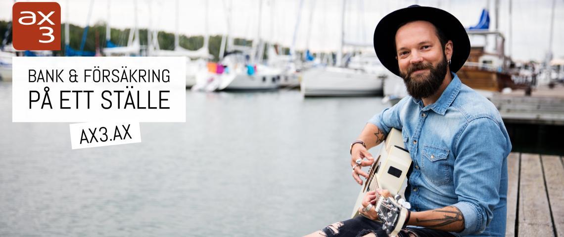 En glad kille spelar på en gitarr på en brygga