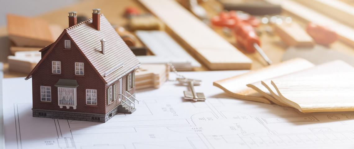 Ett bord med husritningar och en modell av ett hus