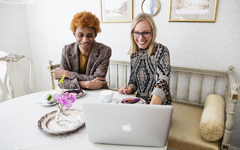 En kille och en tjej på ett café tittar på en dator