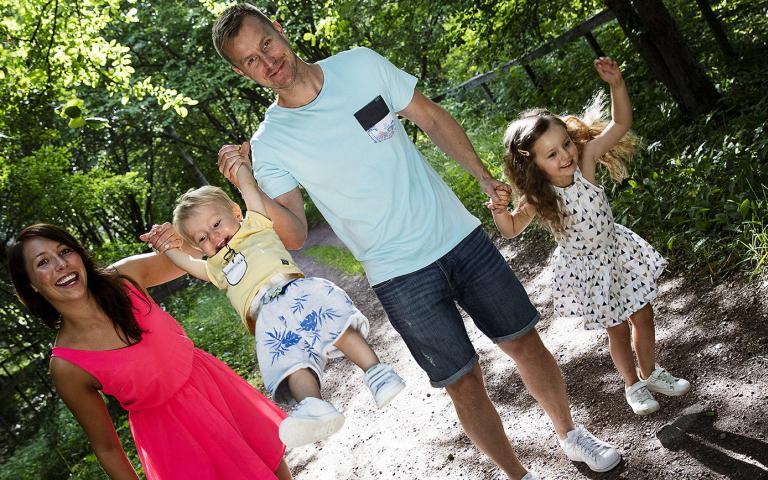 En mamma och en pappa med sina två döttrar i en park.
