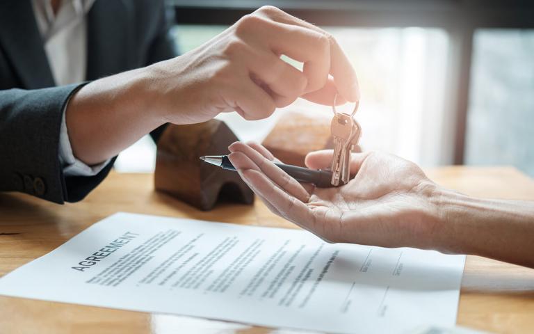 En person som ger en annan person nycklar. På ett bord ligger ett avtal.